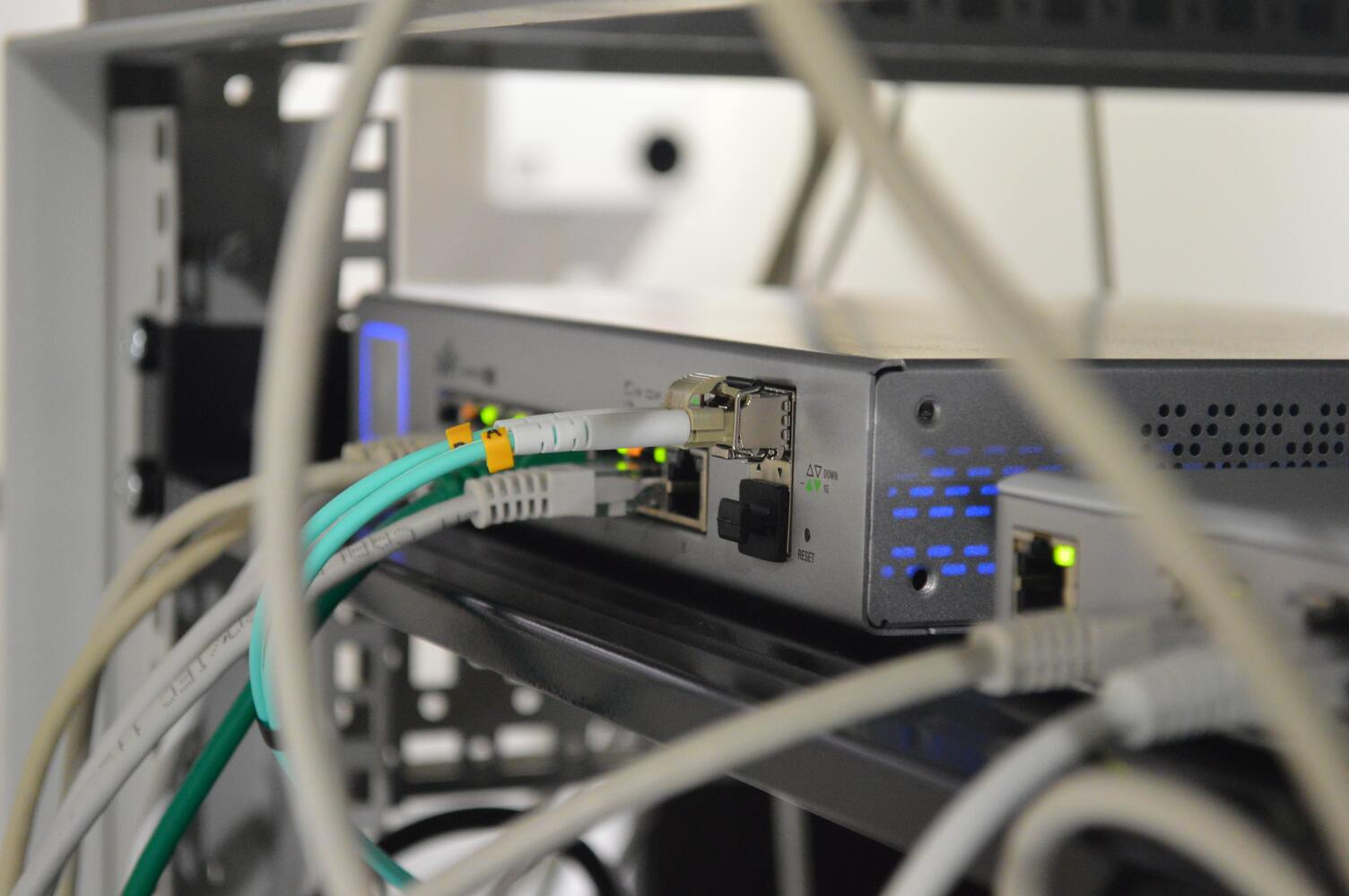 green and gray cords plugged into network engineering computer hardware