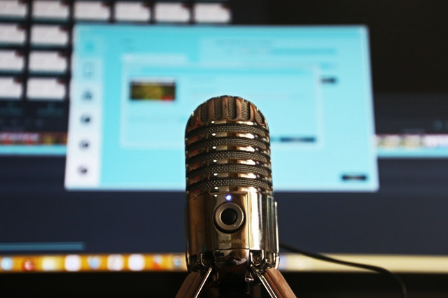 Close-up of a recording microphone with computer and recording software in the background