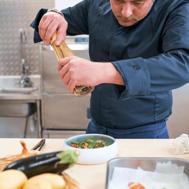un cuisinier qui assaisonne un plat