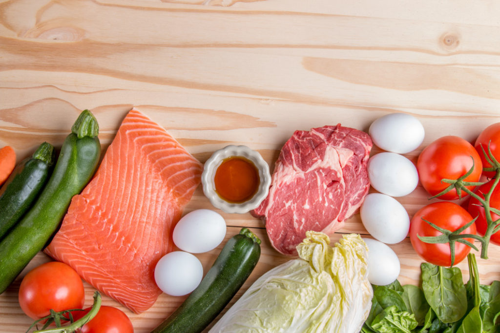 Raw salmon and beef on wooden cutting board, next to cabbage, eggs, tomatoes, carrots, spinach, and zucchini