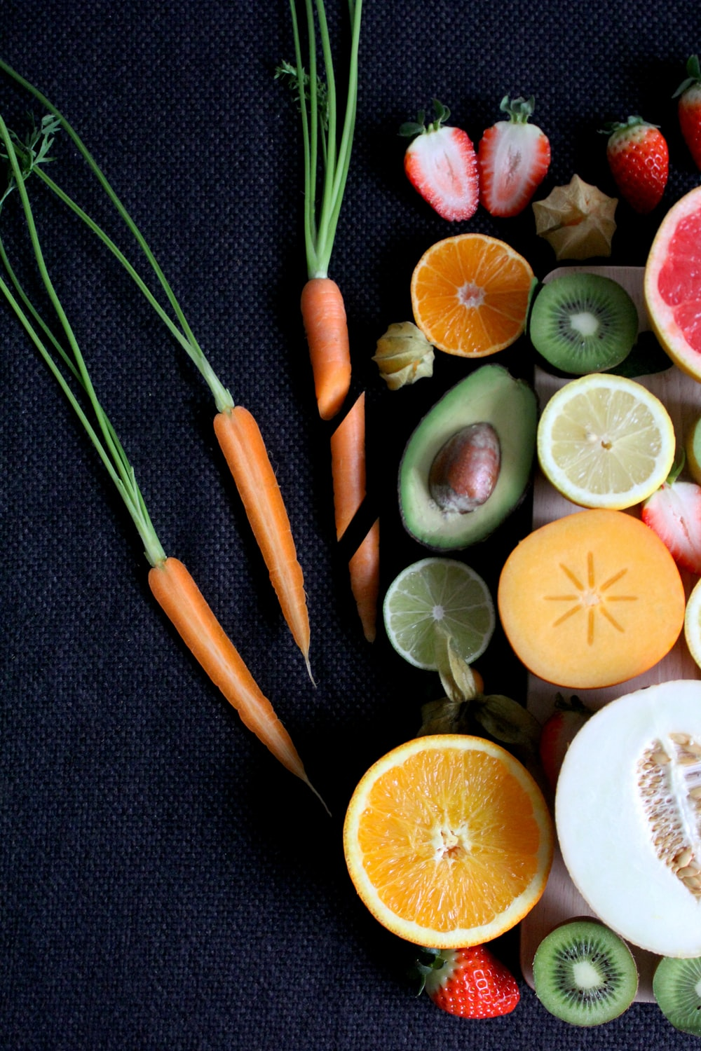 Assortment of sliced vegetable and fruits on board