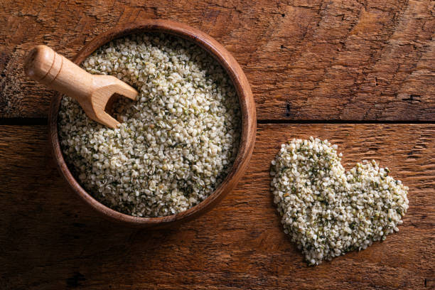 Hemp Seed Hearts Hemp seed hearts on in bowl on a rustic wood top. hemp hearts stock pictures, royalty-free photos & images