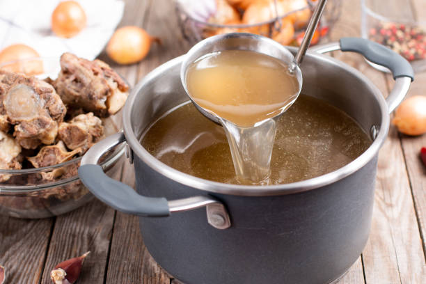 Saucepan with bouillon with a ladle on a wooden table. Bone broth Saucepan with bouillon with a ladle on the table. Bone broth bone broth stock pictures, royalty-free photos & images