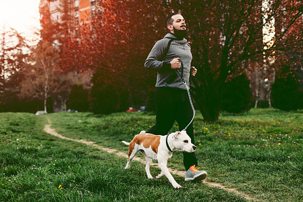 Man Jogging With His Dog during sunset dressed in active wear down a path