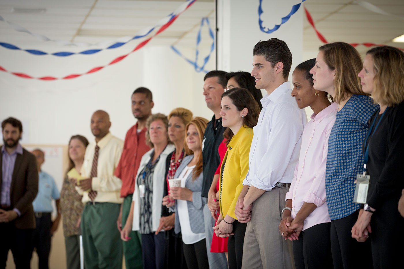 A group of professionals stand in a line with colored party decorations hanging above