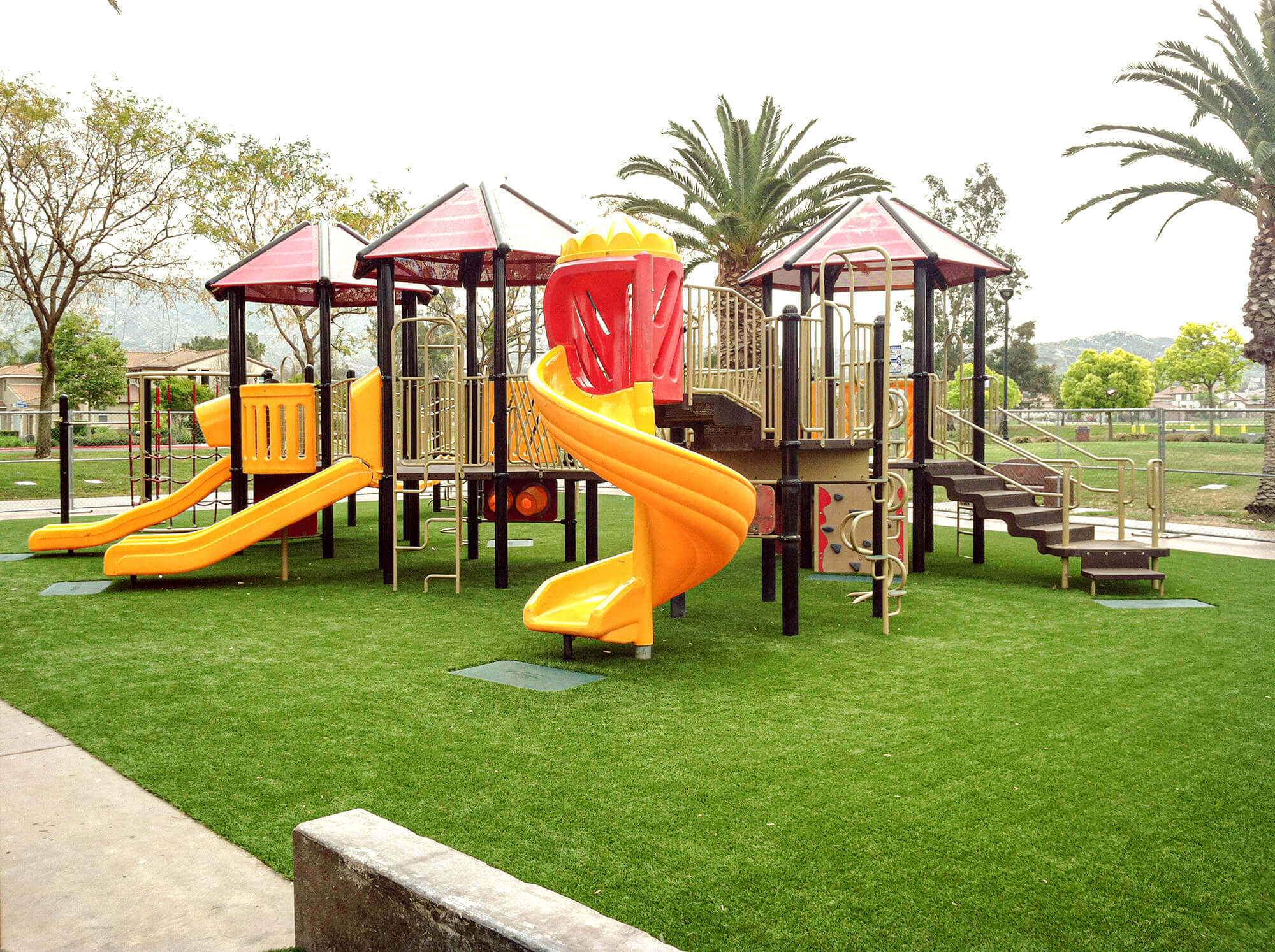 School playground with yellow slide and artificial turf surfacing
