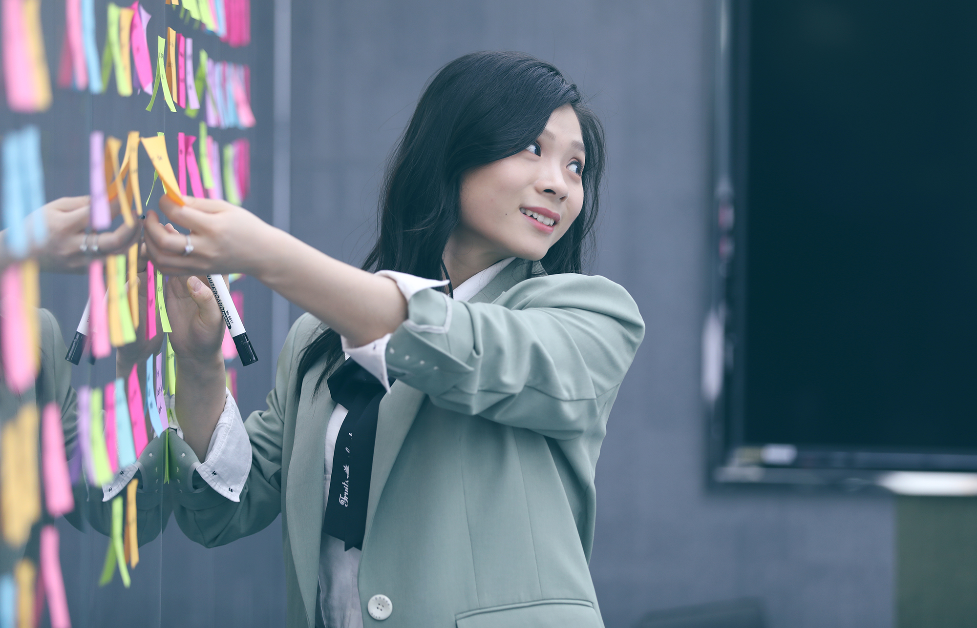 Photo of a Thoughtworks team member adding sticky notes to a board
