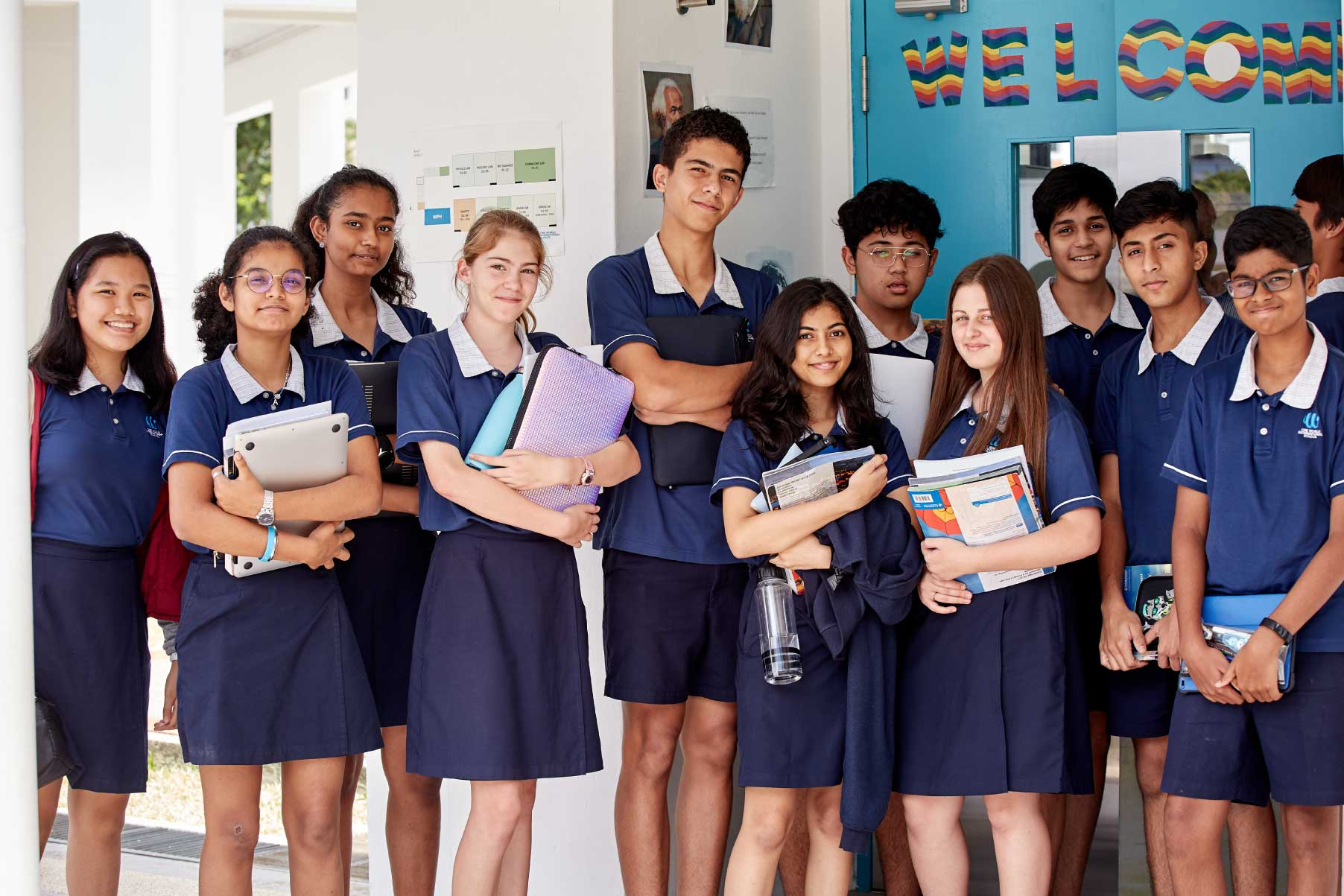 class-of-students-holding-books-posing-for-picture