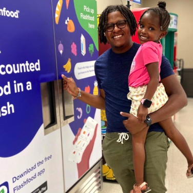 A man and his daughter smiling, standing next to the Flashfood fridge in the store