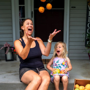 A woman juggling oranges from a Flashfood fruit box with her small daughter sitting next to her laughing