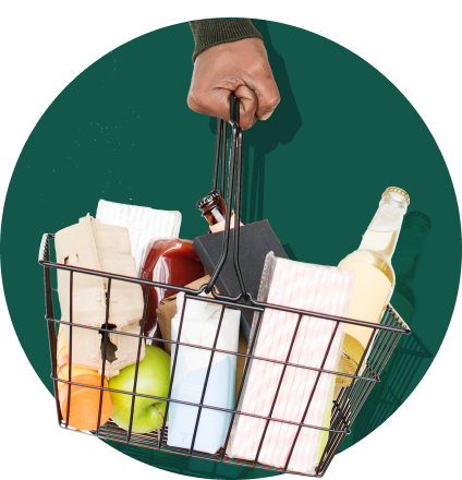 A hand holding a shopping basket with groceries inside