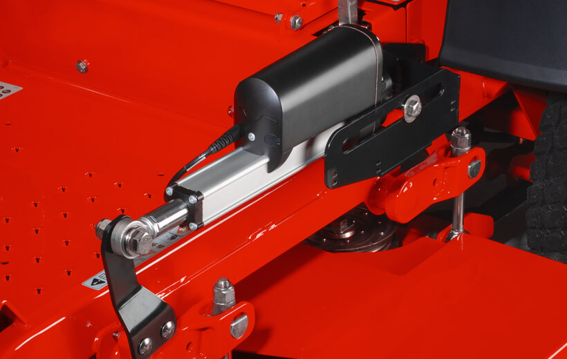 Image of an black electric accuator mounted on a bar above a mower deck