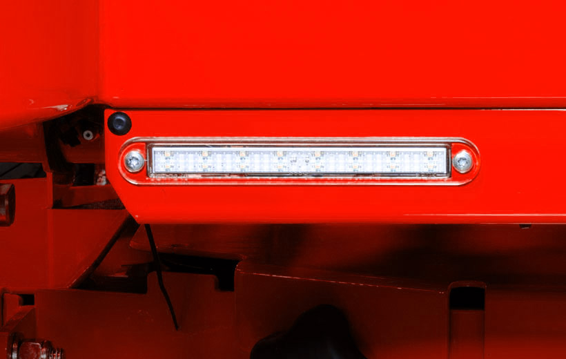 Image of the front of a red mower with a light bar mounted to the frame