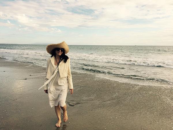 Photo of Cathy Waterman walking on the seashore.
