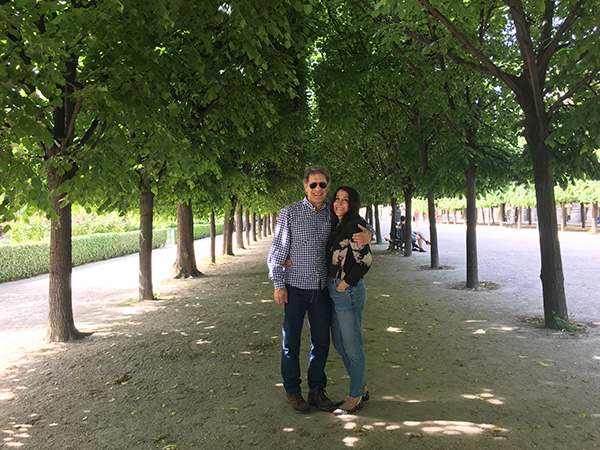 Photo of Cathy Waterman and her husband, Eddie, standing under some trees.