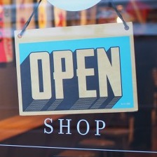 "Blue sign hanging on a business door that says ""Open"" and ""Shop"""