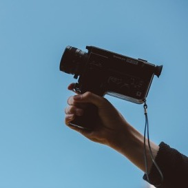 A man's hand holding an old-school video camera from the 70's