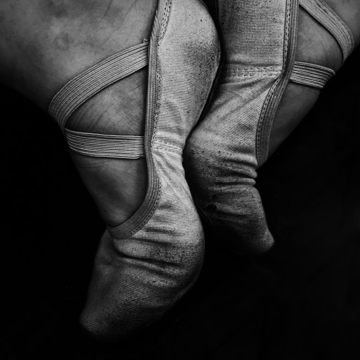 Black and white image of a woman's feet in well-worn ballet shoes