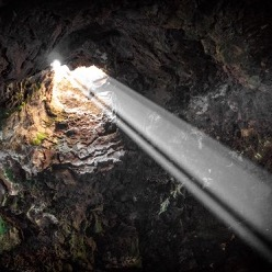 A beam of light shining through a hole in a cave's ceiling