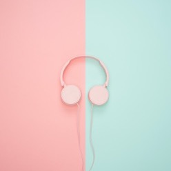 Pink headphones laying on a half pink, half teal background