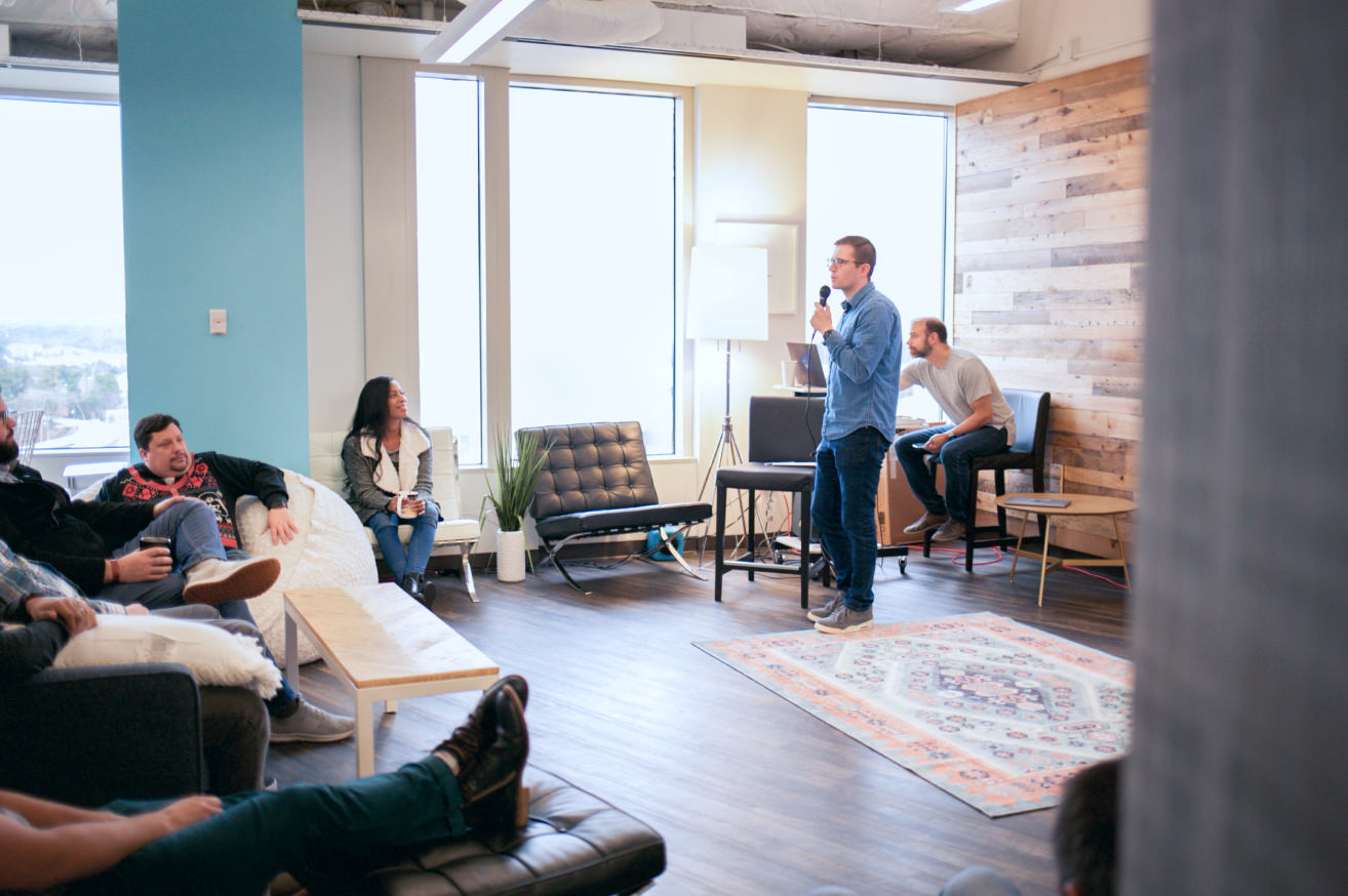 Person speaking to a group in a bright office
