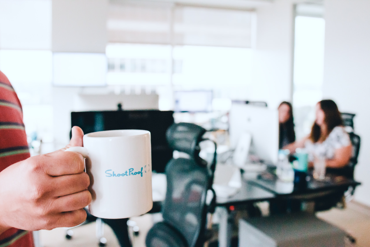 Person holding ShootProof mug in a bright office