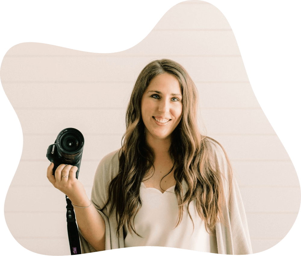 Photo of Logan Fahey holding a camera on a off white background.