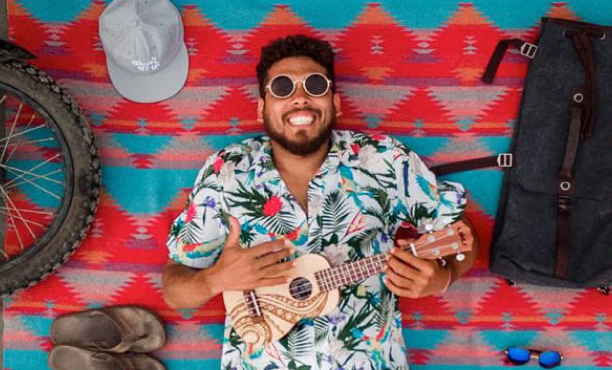 A man in a floral pattern shirt laying on a brightly colored towel wearing sunglasses