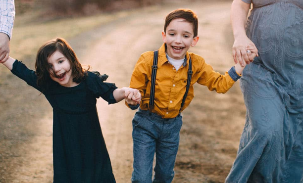 A little boy in a yellow shirt and overalls and a little girl in a black dress holding hands and walking