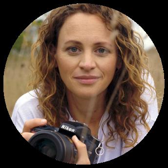Headshot of photographer Jen Bilodeau holding a camera