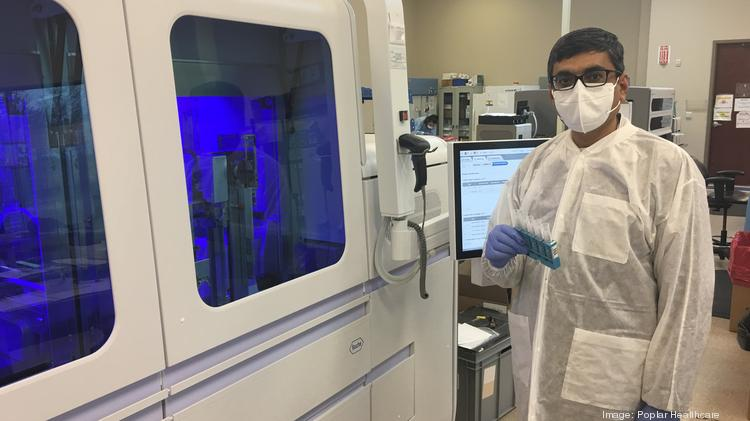 Anami Patel, vice president of genomic operations and development with Poplar Healthcare, standing in front of the Roche Cobas 6800 System used for COVID-19 testing