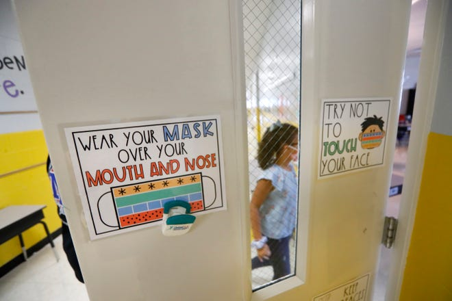 Students return to their classrooms as signage guides proper use of mandated face masks for first and second graders in the hallway at Millington Elementary School on the first day of class Monday, August 10, 2020.