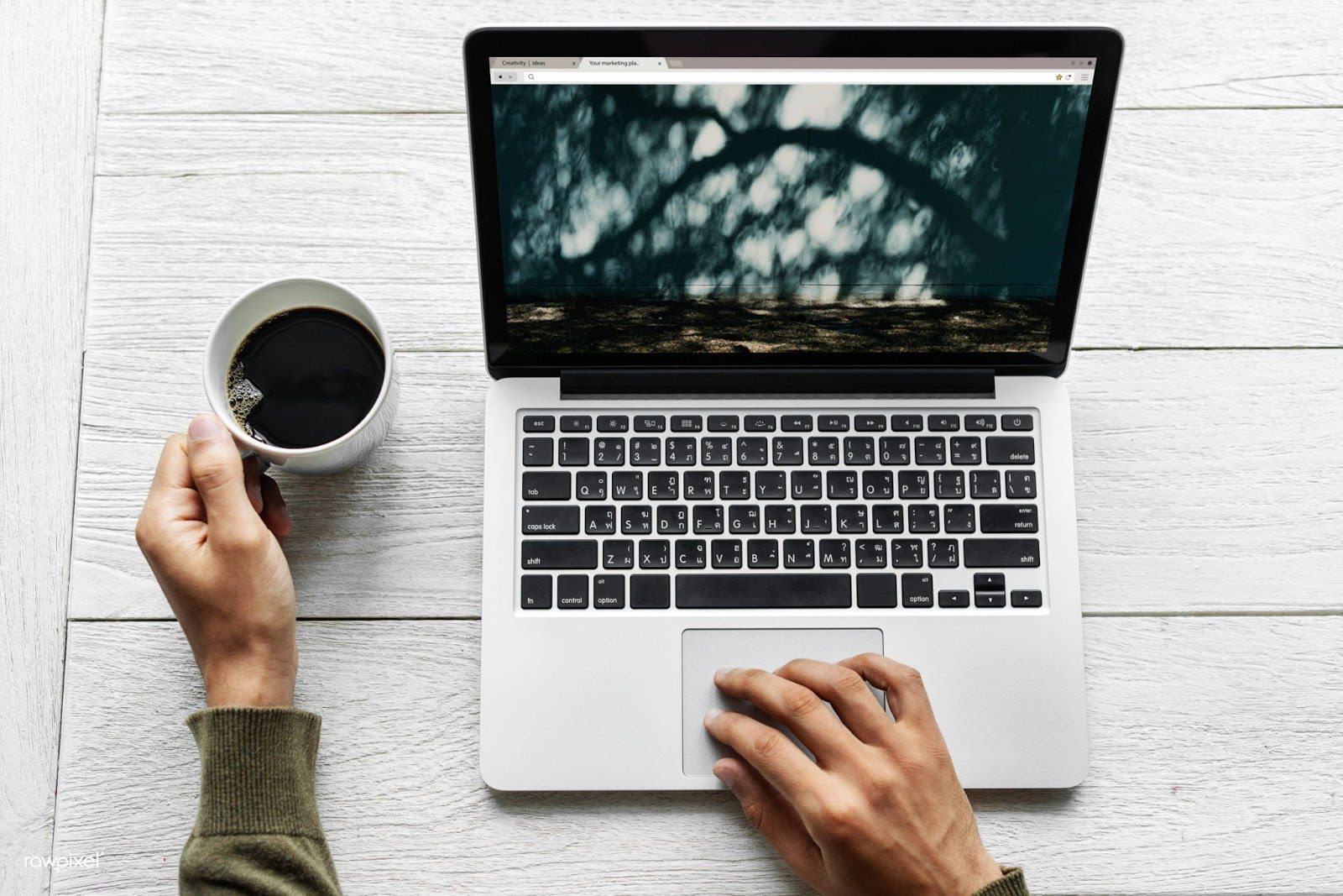 Man with laptop with dark screen and coffee