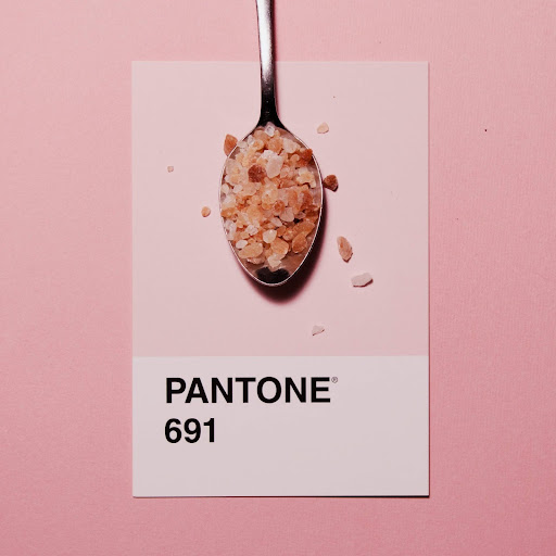 Pantone 691 color swatch with spoonful of Himalayan salt on a light pink background