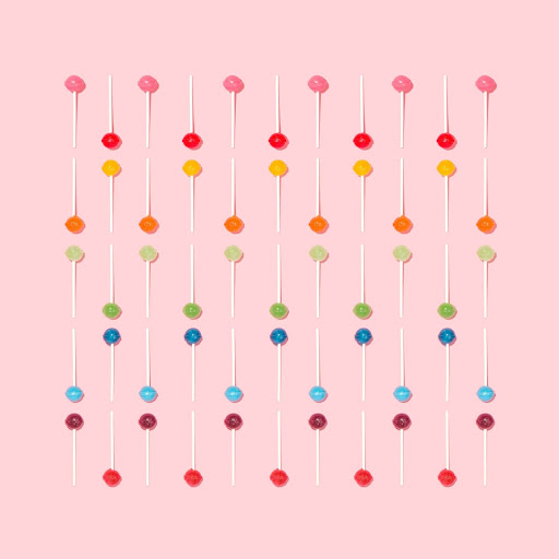 Lollipops arranged by color in a vertical grid pattern, with a light pink background