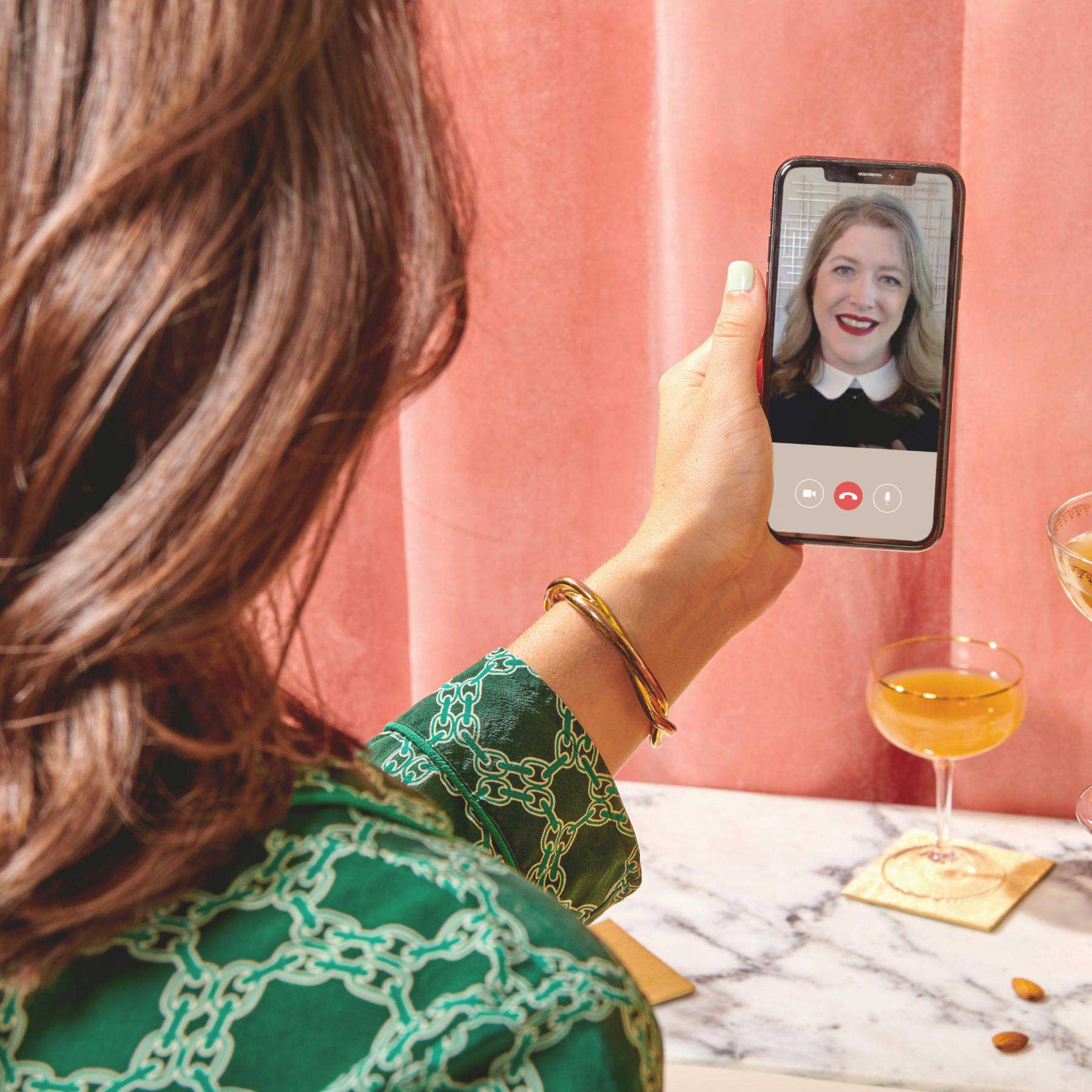 woman looking at phone with money coach on screen