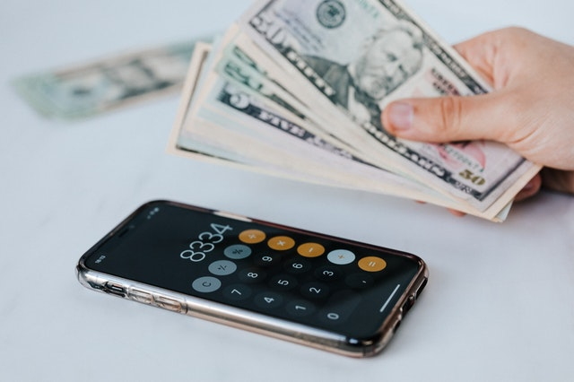 hand holding money with phone calculator