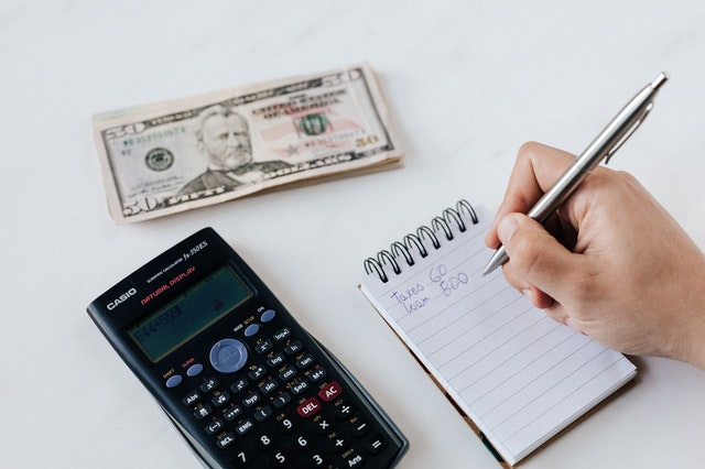 handwriting monthly budget on notepad with calculate and money