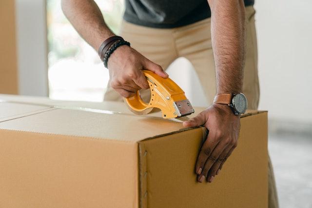 man taping moving box