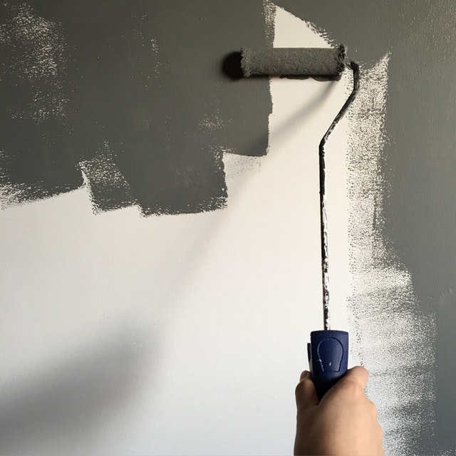 person roller painting their wall gray using home renovation tips