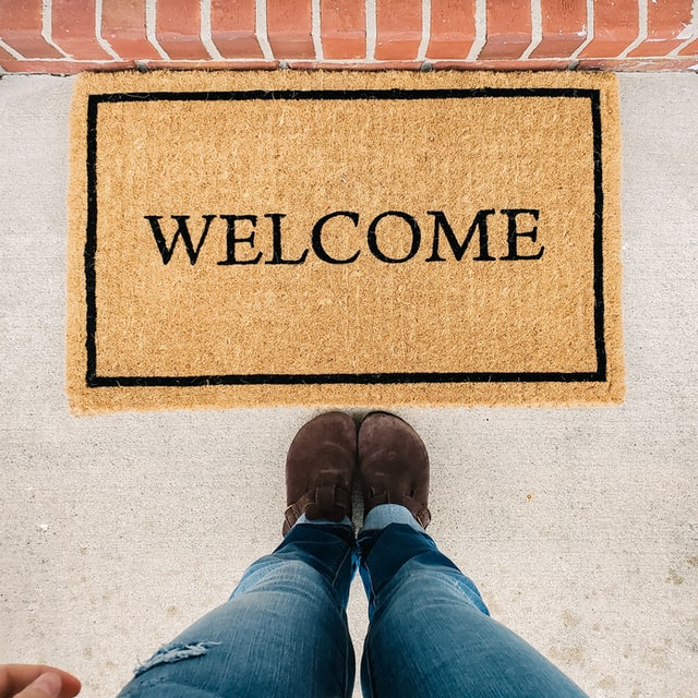 person standing by welcome mat at open house