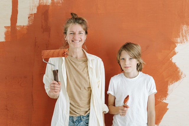 mom and son holding paintbrushes