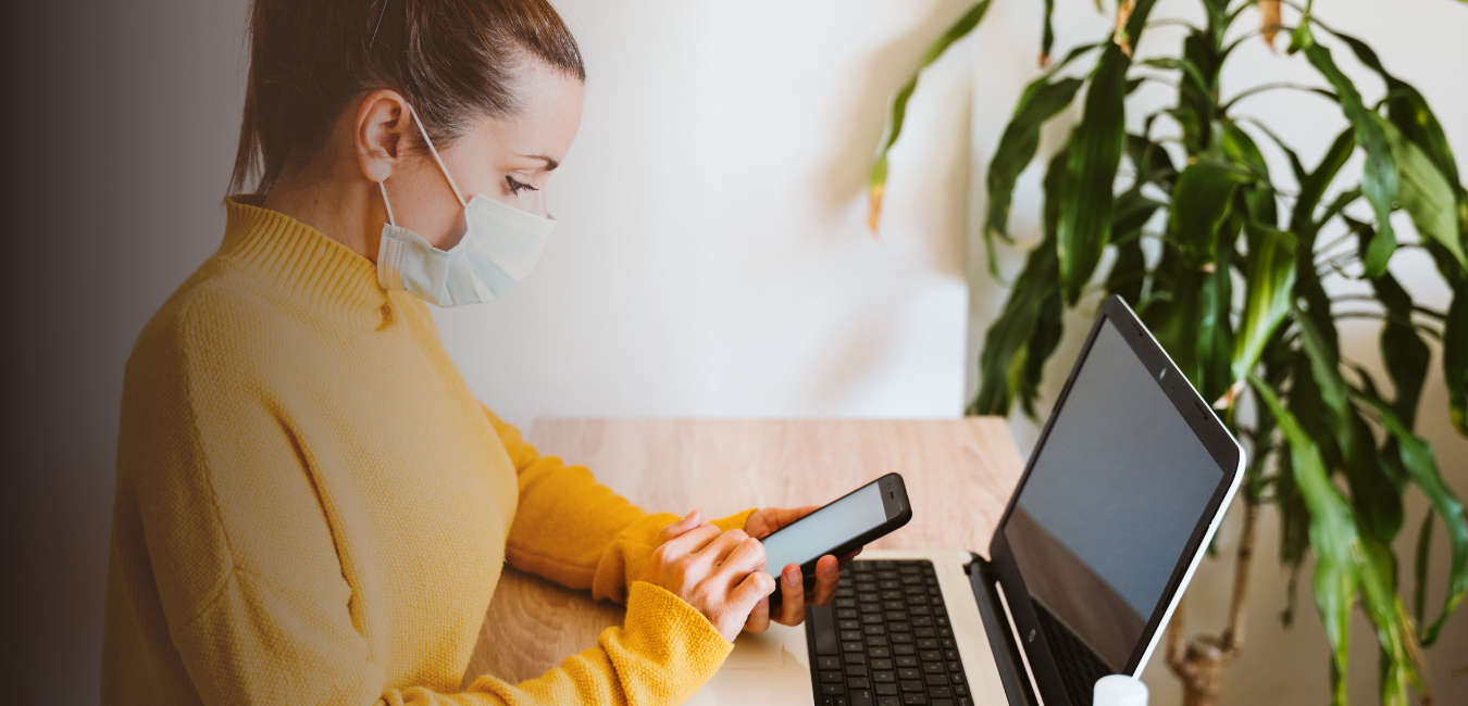 woman wears face mask with iphone and computer