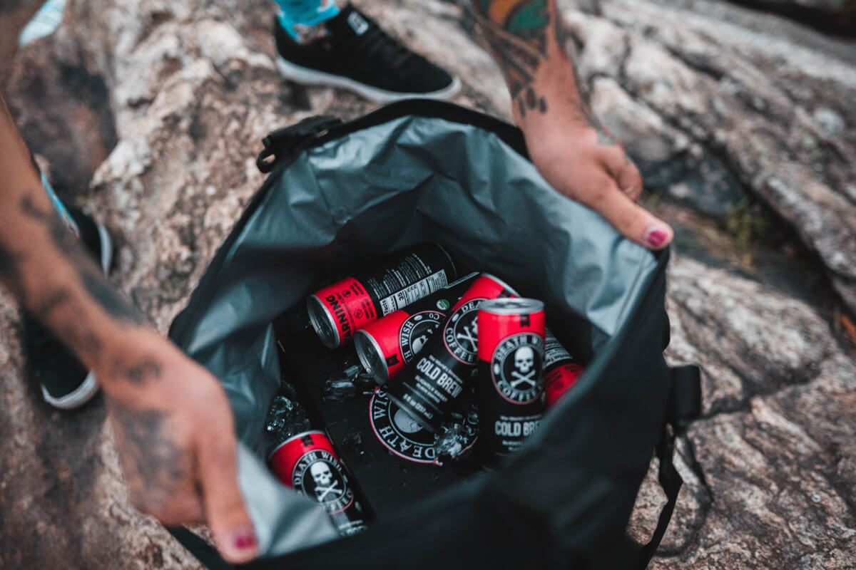 Cans of Death Wish Cold Brew Coffee in a backpack on a hike. Death Wish Coffee use Gorgias for Customer Support