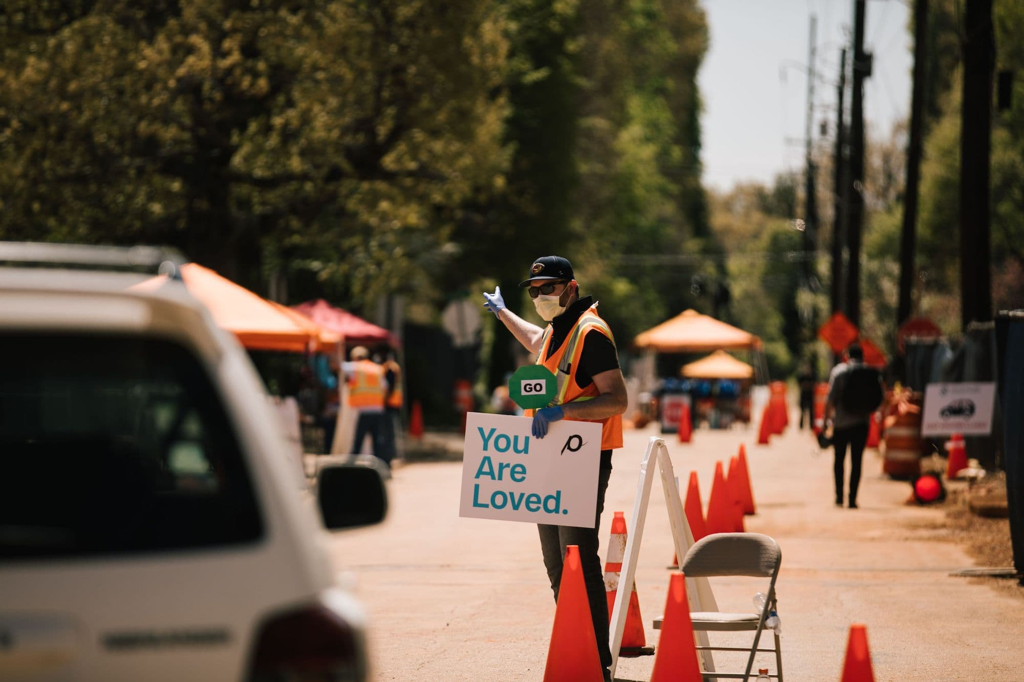 "A man directs traffic while holding a sign that says ""You are loved""."