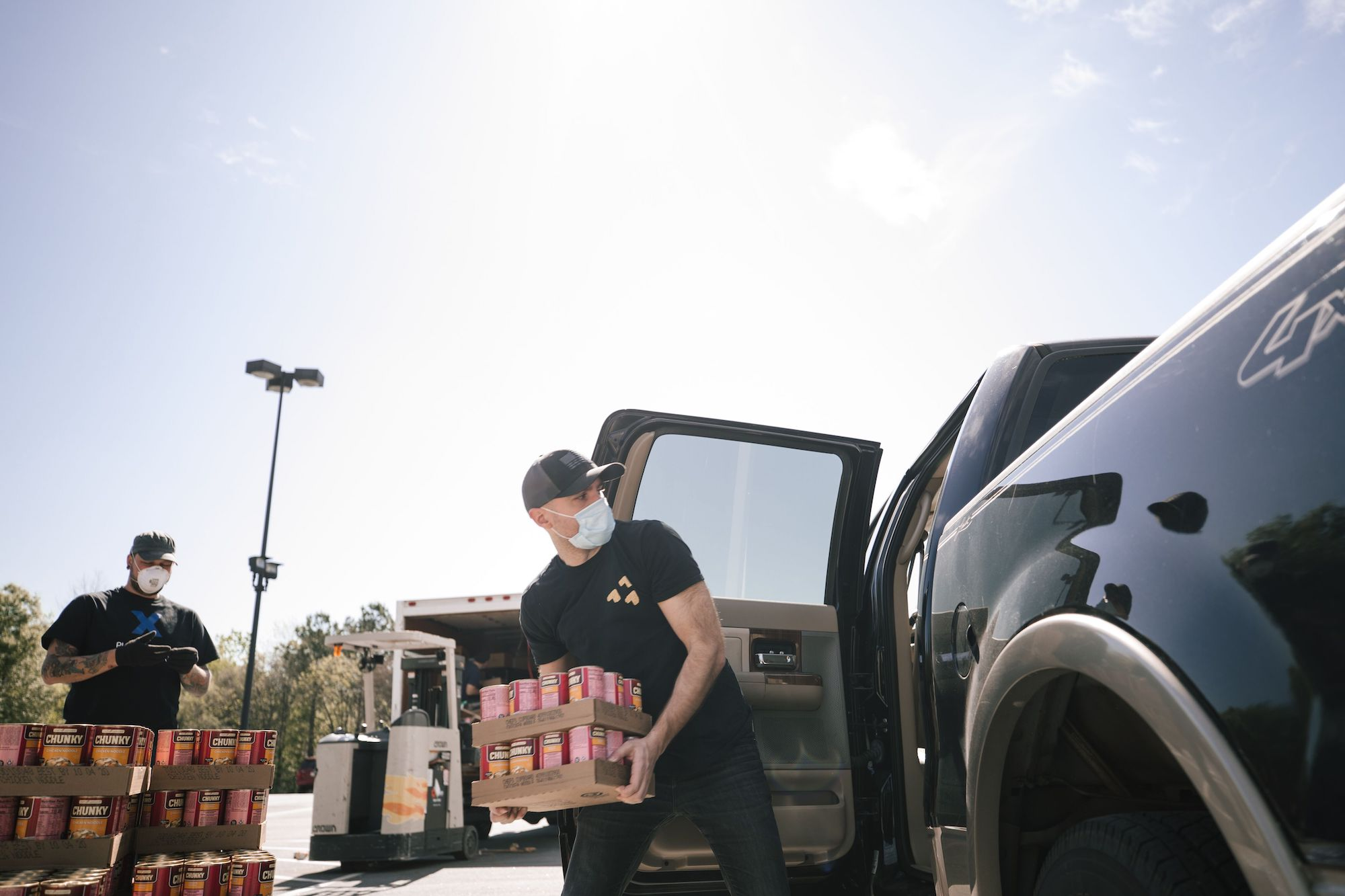 A man unloads canned goods from a truck while wearing a mask.