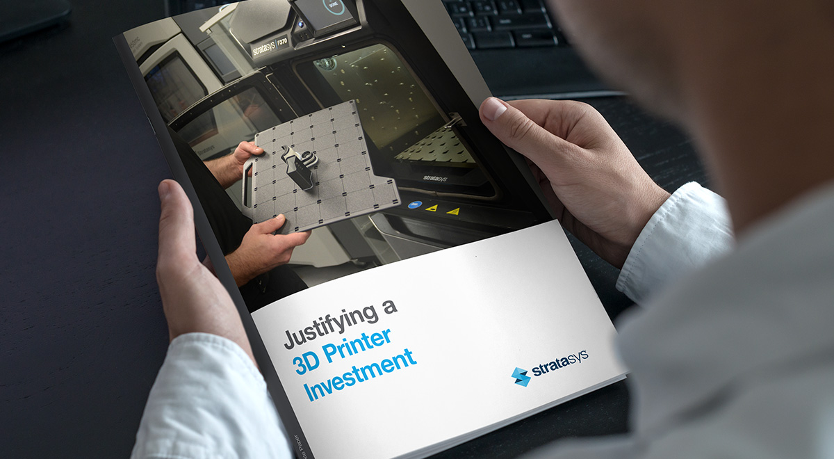 Hands holding the cover of a Stratasys whitepaper, showing a 3D printer.
