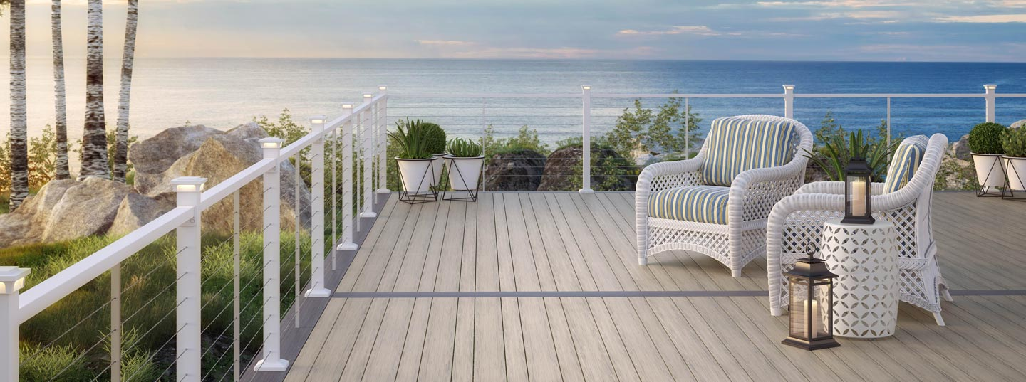 Grey deck with white railing and furniture, overlooking a body of water.