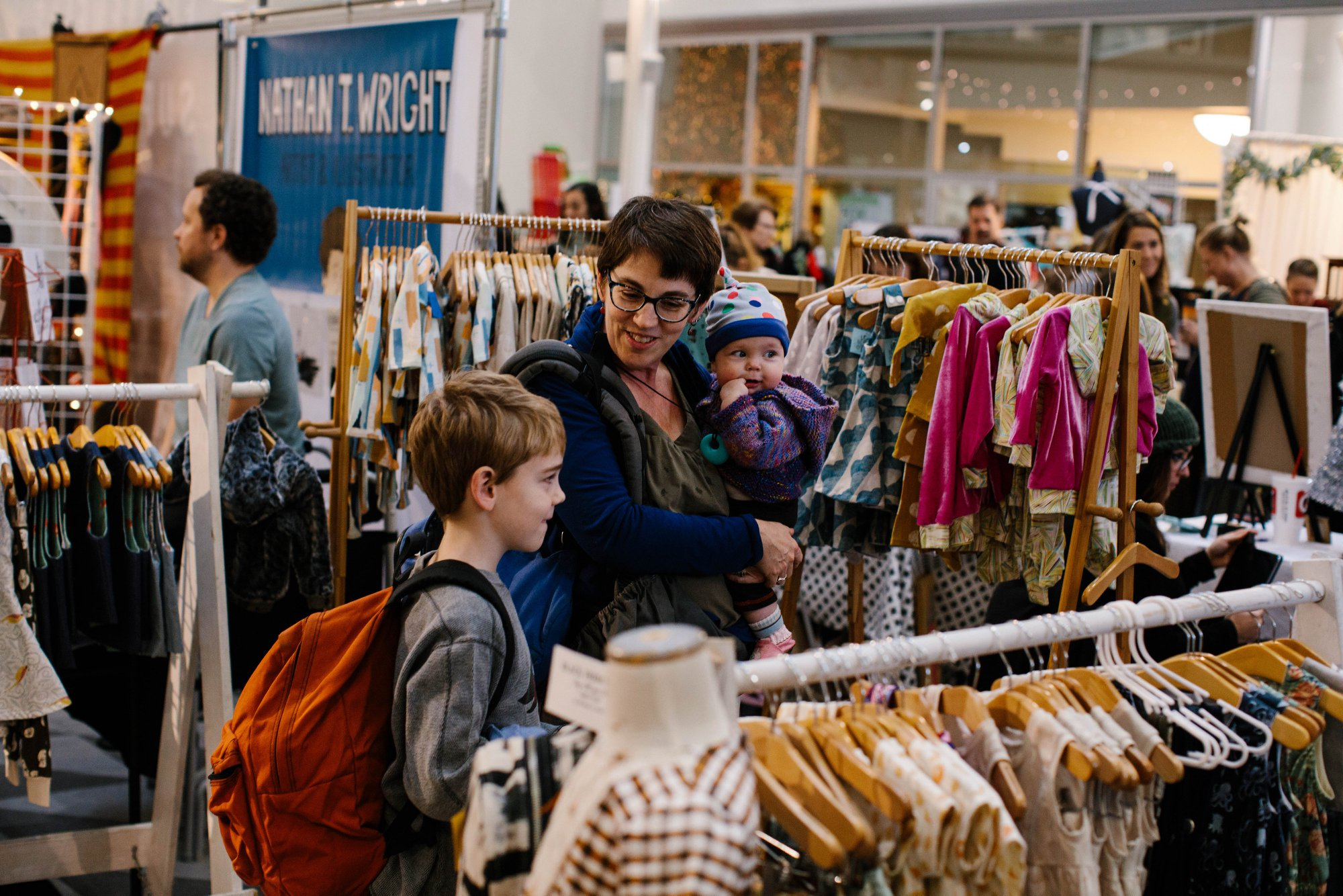 A family standing in front of a children's clothing rack.