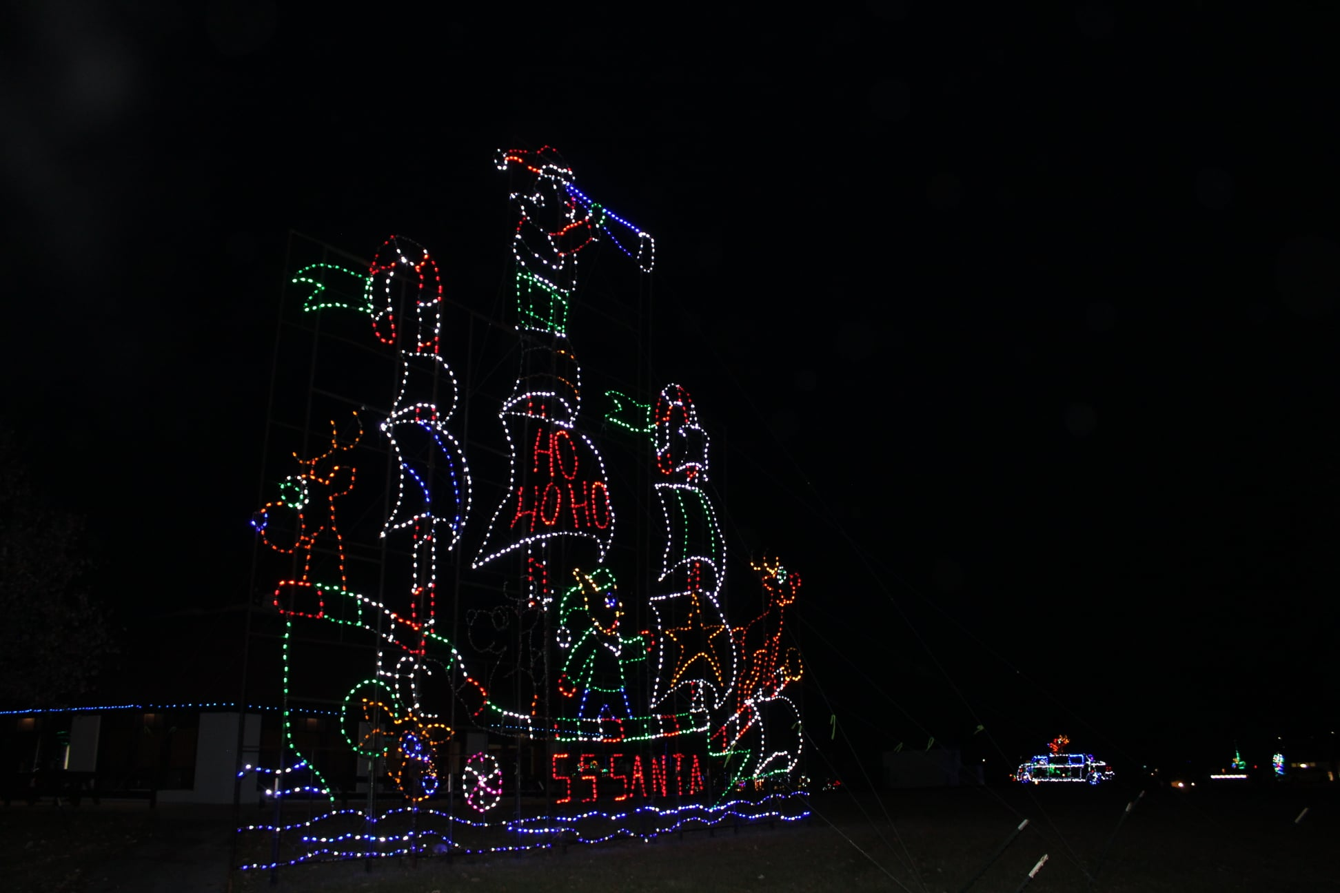 Holiday light display against  a black night sky.